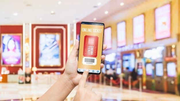 Mão de telefone móvel de maquete usando o smartphone para o conceito de bilhetes de cinema on-line