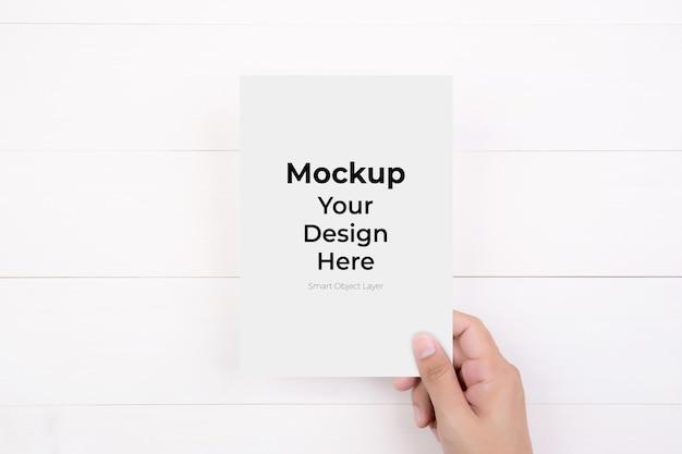 Mão de um jovem segurando cartaz ou maquete de cartão