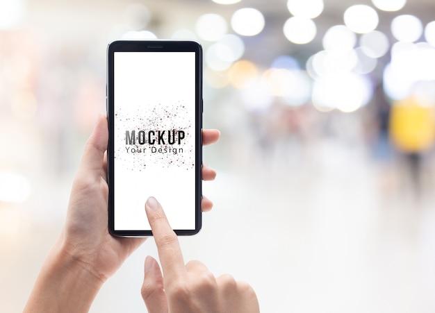 Mão de uma mulher segurando e tocando smartphone preto com modelo de maquete de tela em branco