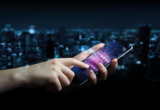 Mão de uma mulher segurando o smartphone moderno no maquete escuro