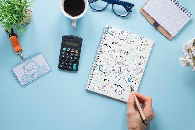 Mão de vista superior, escrevendo em uma maquete de notebook