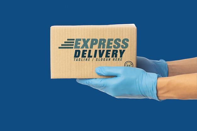 Mão do entregador closeup em luvas médicas segurando maquete de caixa de papelão