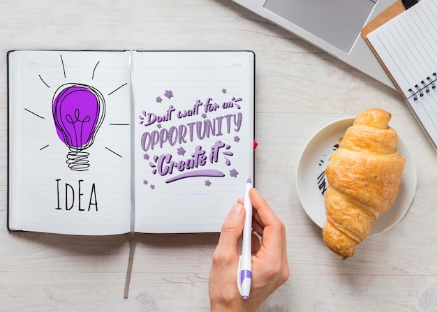 Mão escrevendo algo em uma maquete de caderno