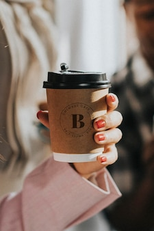 Mão feminina segurando uma maquete de xícara de café