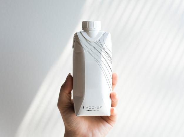 Mão humana segurando maquete de garrafa de papel