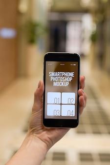 Mão humana segurando smartphone moderno +