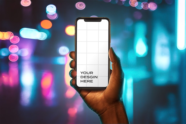 Mão mão segurando nova maquete de smartphone com bokeh