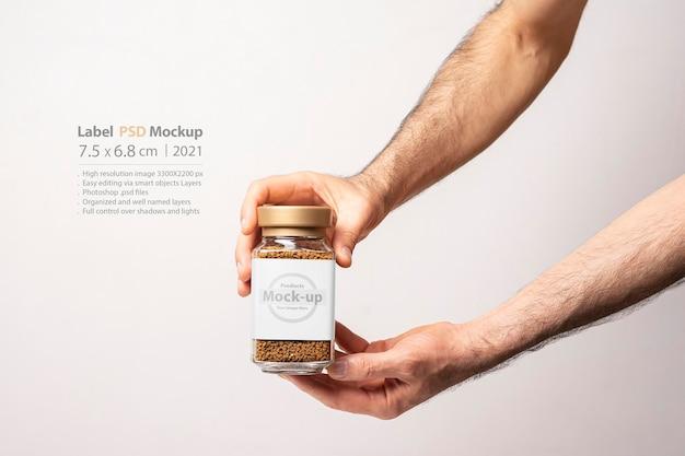 Mão masculina segurando uma maquete de frasco de vidro de café instantâneo