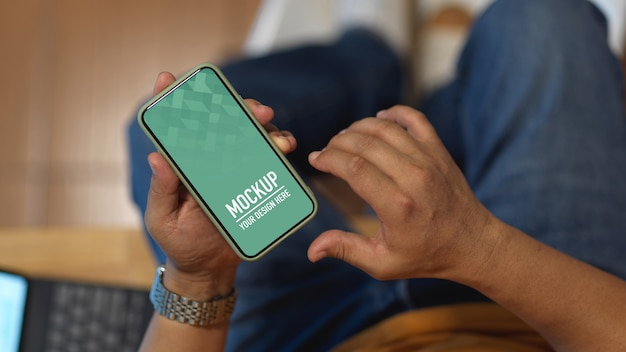 Mão masculina usando maquete de smartphone enquanto está sentado na sala de escritório