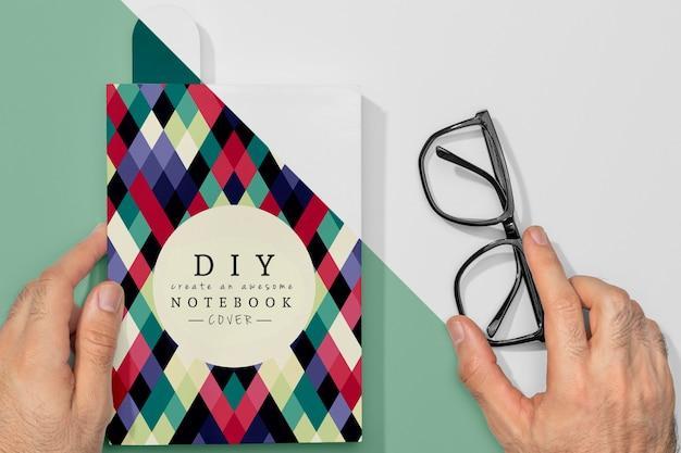 Mão plana segurando a maquete do livro e óculos