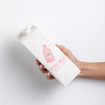 Mão segurando a caixa de leite com maquete