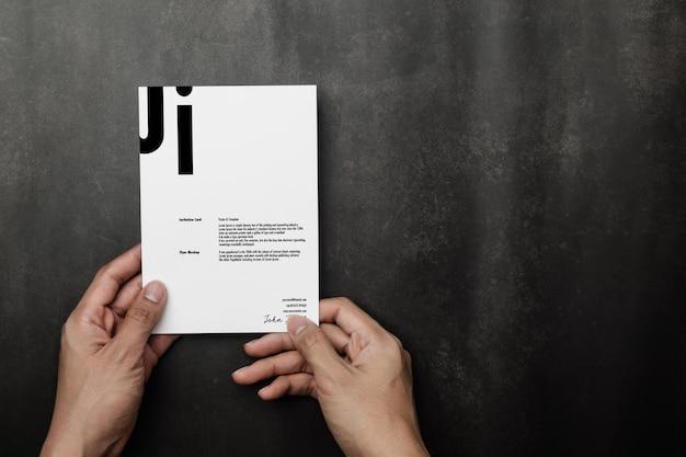 Mão segurando a maquete de cartão de convite, modelo de cartão de visita.