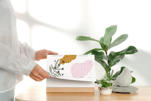 Mão segurando a maquete do calendário em espiral de papel em branco