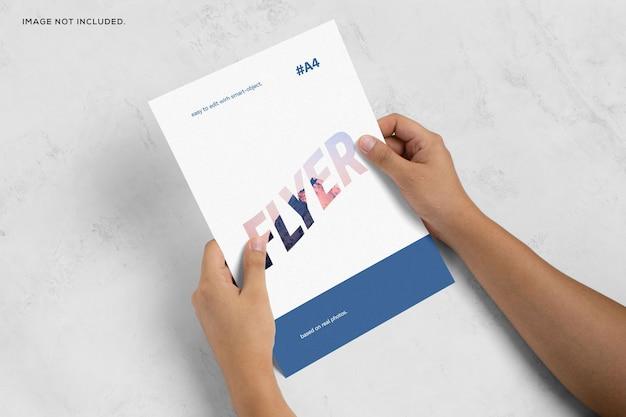 Mão segurando a maquete do panfleto