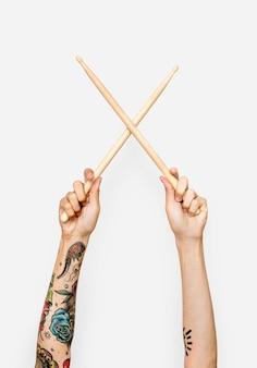 Mão segurando baquetas