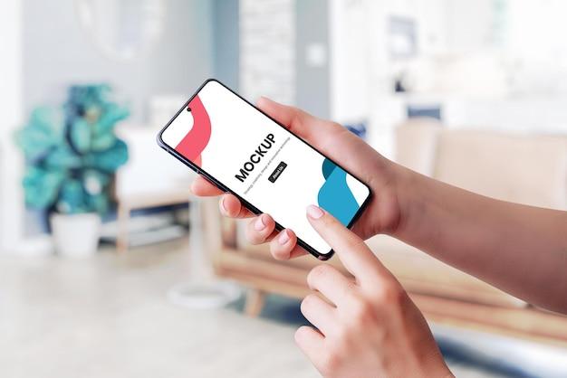 Mão segurando maquete de smartphone e tela tocante