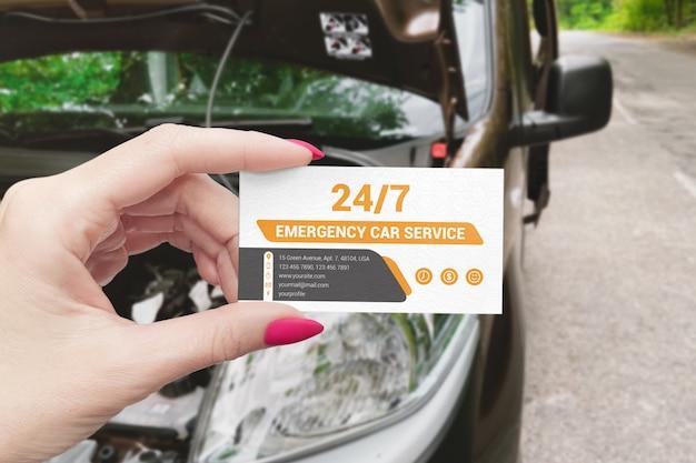 Mão segurando o cartão de visita perto de uma maquete de cena de carro quebrado