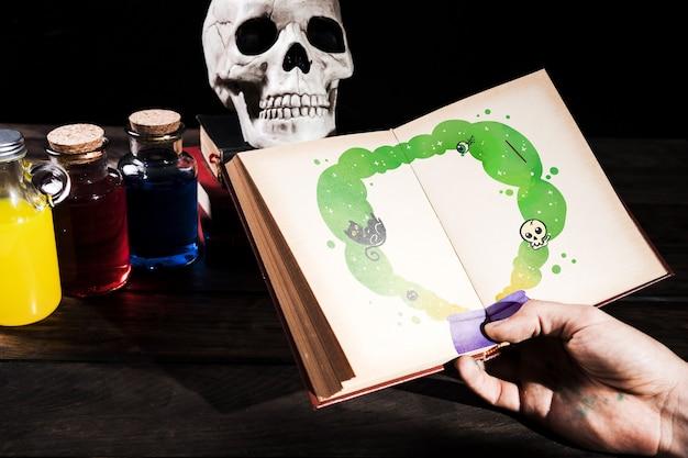 Mão segurando o livro com desenhos e garrafas de veneno