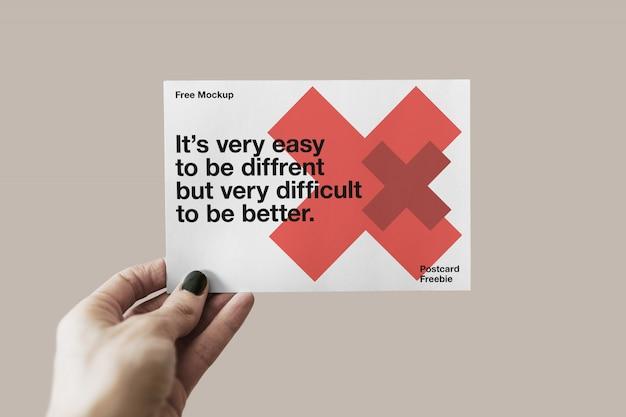 Mão segurando o maquete de cartão postal