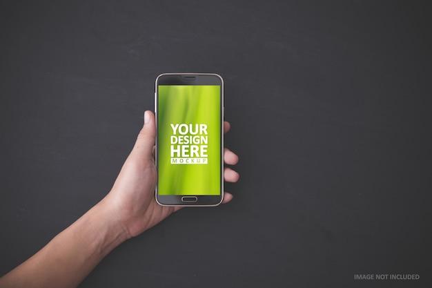 Mão segurando o smartphone, maquete.