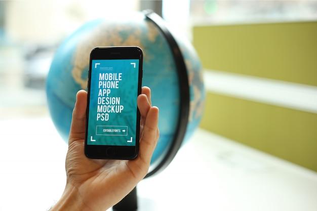 Mão segurando o smartphone por trás da maquete do globo psd