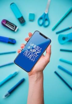 Mão segurando o telefone com moldura de ferramentas