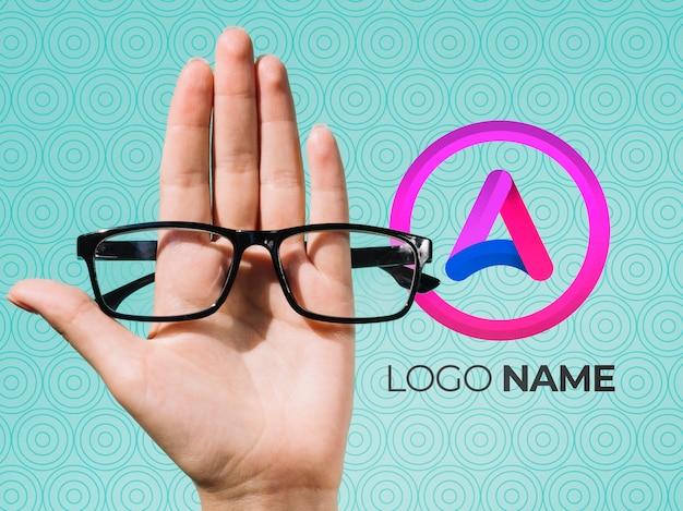 Mão segurando óculos e design de nome de logotipo