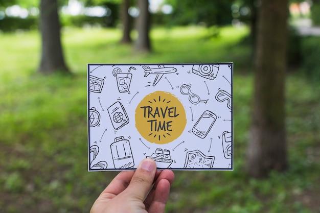 Mão segurando papel na natureza para o conceito de viagens