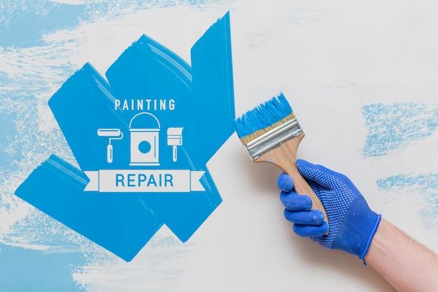 Mão segurando um pincel com cor azul