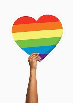Mão segurando um suporte de papelão de coração de arco-íris