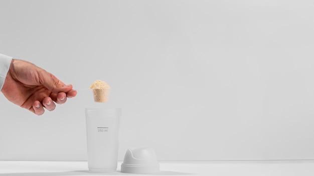 Mão segurando uma colher de fitness cheia de proteína acima do espaço de cópia do shaker