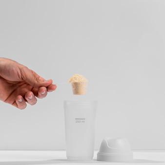 Mão segurando uma colher de fitness cheia de proteína acima do shaker