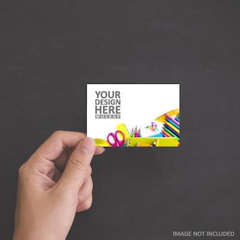 Mão segurando uma maquete de cartão branco em branco
