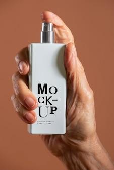 Mão segurando uma maquete de frasco de spray recarregável branco