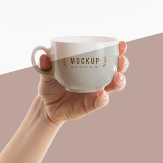 Mão segurando uma maquete de xícara