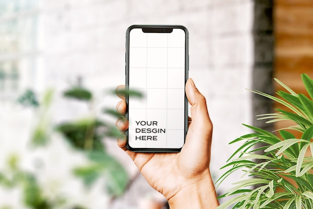 Mão segurando uma nova maquete de smartphone cercada por folhas