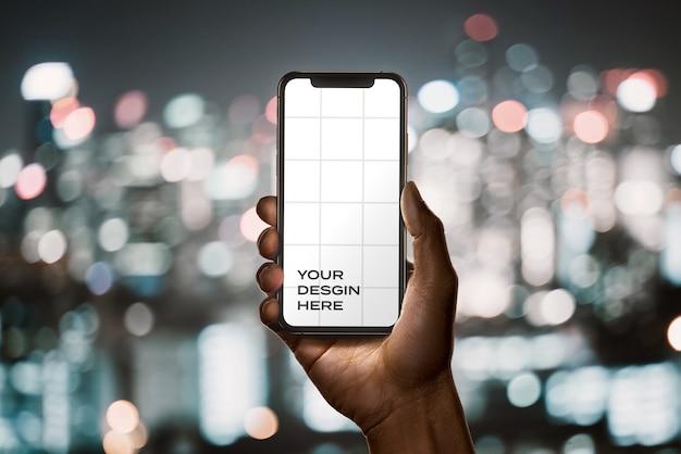 Mão segurando uma nova maquete de smartphone com bokeh