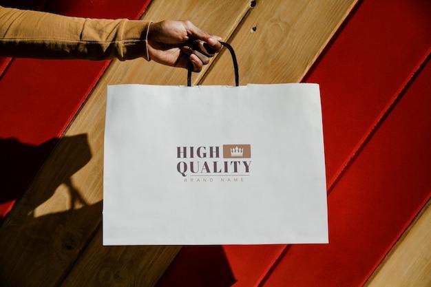 Mão segurando uma sacola de compras no centro