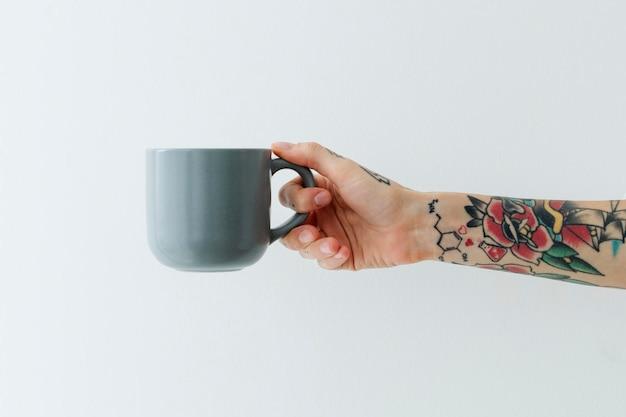 Mão tatuada segurando uma xícara de café azul cinza