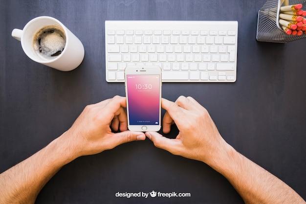 Mãos com telefone e mesa de escritório