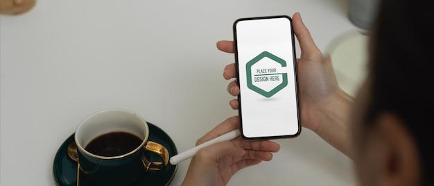 Mãos de alunos usando maquete de smartphone no escritório