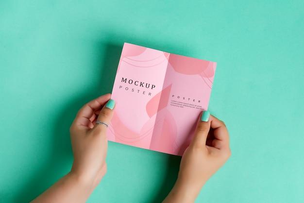 Mãos de mulher estão segurando brochura de papel mock-up vazio