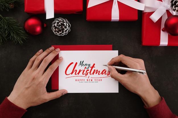 Mãos escrevendo maquete de cartão de feliz natal com decorações de presentes de natal