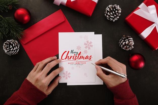 Mãos escrevendo maquete de cartão de feliz natal com decorações de presentes