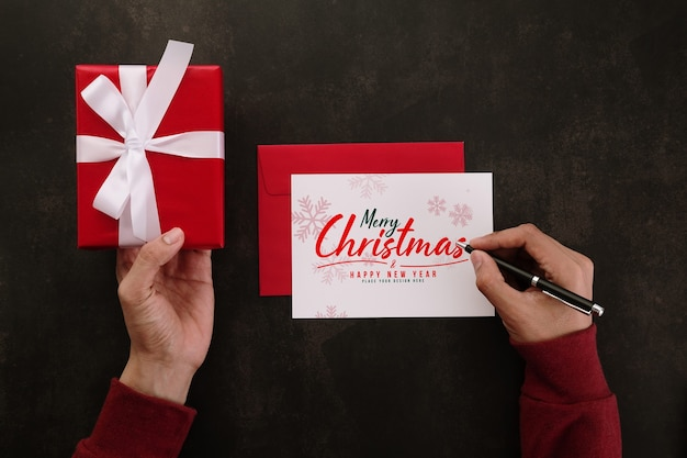 Mãos escrevendo maquete de cartão de feliz natal