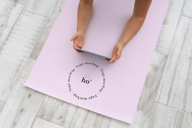 Mãos femininas em maquete de tapete de ioga