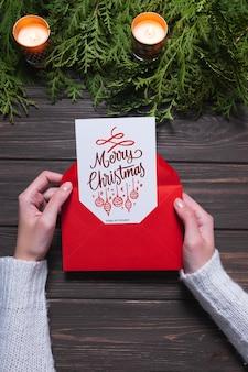 Mãos femininas estão segurando um cartão de natal e um envelope. atmosfera festiva na época do natal. brincar