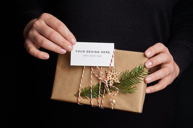 Mãos femininas segurando uma caixa de presente de natal com maquete de cartão de visita