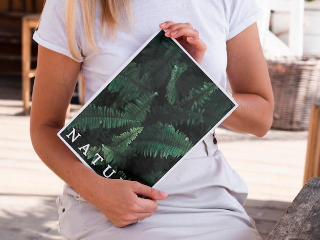 Mãos mostrando uma revista natureza mock up