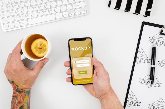 Mãos planas segurando uma maquete de smartphone e chá